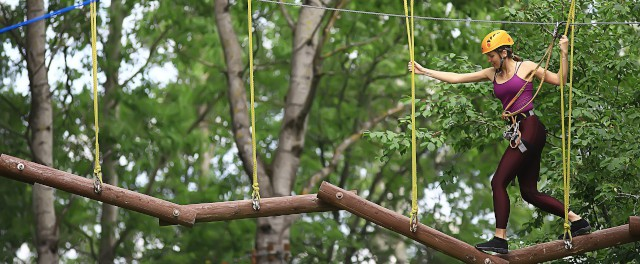 woman in pink top does high wire assault course